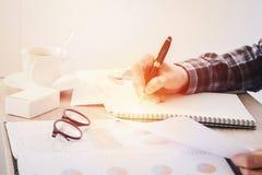 商人文字的手某事在笔记本纸和企业财务在桌上弄脏的报告文件 库存图片