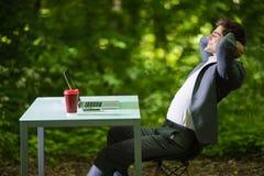 商人旁边画象在工作以后放松了在办公桌上的膝上型计算机在绿色公园 到达天空的企业概念金黄回归键所有权 免版税图库摄影