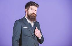 商人时兴的成套装备立场紫罗兰色背景 人有胡子的行家穿经典衣服服装 正式成套装备 库存照片