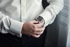 商人时钟衣裳,检查在他的wris的商人时间 免版税库存图片