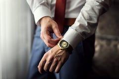 商人时钟衣裳,检查在他的wris的商人时间 免版税库存照片