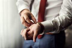 商人时钟衣裳,检查在他的wris的商人时间 免版税图库摄影