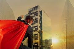 商人是企业大厦背景的o一个超级英雄 免版税库存图片