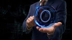 商人显示概念在他的手上的全息图3d时钟 库存图片
