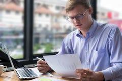 商人有经营计划文件的用途膝上型计算机在工作场所 免版税库存图片