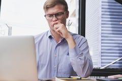 商人有经营计划的用途膝上型计算机在工作场所 人工作 免版税库存照片