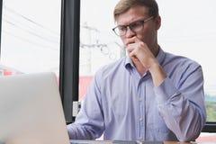 商人有经营计划的用途膝上型计算机在工作场所 人工作 免版税库存图片