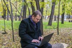 商人有膝上型计算机在秋天的公园 年轻人坐树在有膝上型计算机的公园在他的膝部和检查电子邮件 库存图片