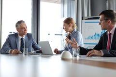 商人有讨论在桌上在证券交易经纪人行情室 免版税库存图片