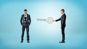 商人朝有在他的躯干的一个黑暗的匙孔的另一个人的方向把握一个巨型关键 库存图片