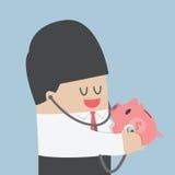 商人检查存钱罐的健康用途听诊器 免版税库存照片