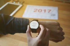 商人检查的时间神色smartwatch对见面在咖啡店 库存图片