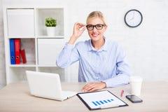 商人概念-坐在办公室的成功的女商人画象  库存照片