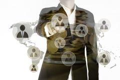 商人点两次曝光手指代表主导的队和金黄硬币在瓶子,领导概念 库存照片