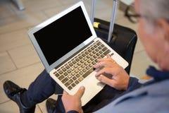 商人特写镜头使用膝上型计算机的在机场大厅 免版税库存图片