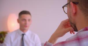 商人特写镜头后面视图画象在玻璃的谈话与他的年轻伙伴在办公室户内 股票视频