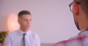 商人特写镜头后面视图画象在镜片的谈话与他的年轻伙伴在办公室户内 影视素材