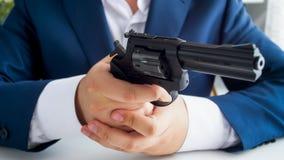 商人特写镜头照片在坐在办公室和拿着左轮手枪的衣服的 免版税库存照片