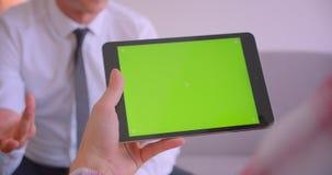 商人特写镜头画象谈话与他的有绿色色度关键屏幕的伙伴片剂在办公室 股票视频