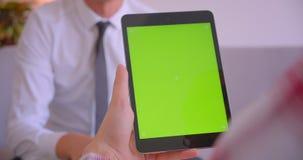 商人特写镜头画象谈话与客户有绿色色度关键屏幕的藏品片剂在办公室 影视素材