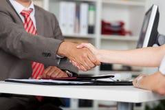 商人特写镜头与女性候选人握手 免版税库存照片