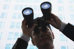 年轻商人特写镜头使用双筒望远镜和看的 库存照片