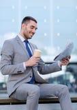 年轻商人用咖啡和报纸 免版税库存照片