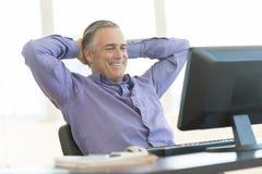 商人用在看计算机的头后的手在办公室 免版税库存图片
