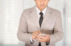 商人用途一个智能手机在办公室 免版税库存照片