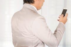 商人用途一个智能手机在办公室 库存图片