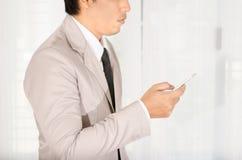 商人用途一个智能手机在办公室 免版税库存图片