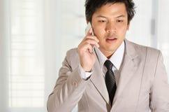 商人用途一个智能手机在办公室 免版税图库摄影