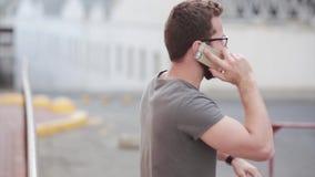 年轻商人由智能手机情感地谈话,有问题 戴胡子和眼镜的人使用在街道上的电话 股票视频