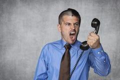 商人由电话卸载在雇员的愤怒 库存图片