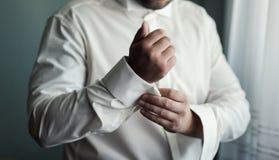 商人男式衬衫 白色衬衣的人在windo 免版税库存照片