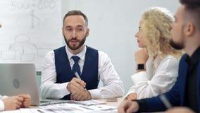 商人男性teamleader佩带的领带谈和谈论工作与同事队会议 股票视频
