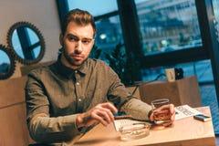 商人画象与雪茄和杯的威士忌酒在坐在桌上的手上 库存照片