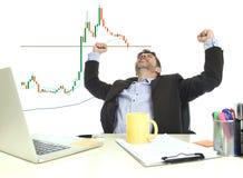 商人疯狂愉快在赢取外汇以后或股票换在办公计算机书桌庆祝 免版税库存照片