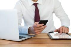 商人的中央部位使用手机和数字式片剂的有在桌上的膝上型计算机的 库存照片