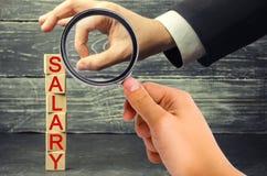 商人的手去除一个木块与题字薪金 薪金减少 薪水裁减  减少的赢利和 免版税库存照片