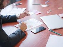 商人的手在一张桌上的在纸后 图库摄影