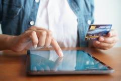 商人的接近的手在网上买与信用卡 人使用片剂并且做着网上交易 免版税库存图片