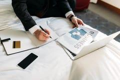 商人的播种的图象坐与报纸的床 免版税库存图片