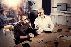 商人的概念群策群力过程的 做在笔记本的有胡子的成人人笔记 在现代的工友配合 免版税库存照片