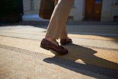 商人的脚走在行人穿越道斑马的 免版税库存照片