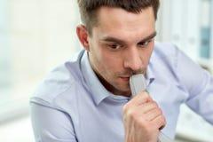商人的面孔与电话接收器的在办公室 库存图片