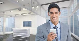 商人的综合图象使用手机的有后边同事的 免版税图库摄影