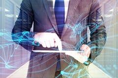 商人的综合图象使用他的片剂个人计算机的 免版税图库摄影