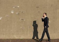 商人的画象走和谈话在手机 库存照片