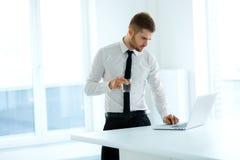 商人研究他的计算机在办公室 库存照片